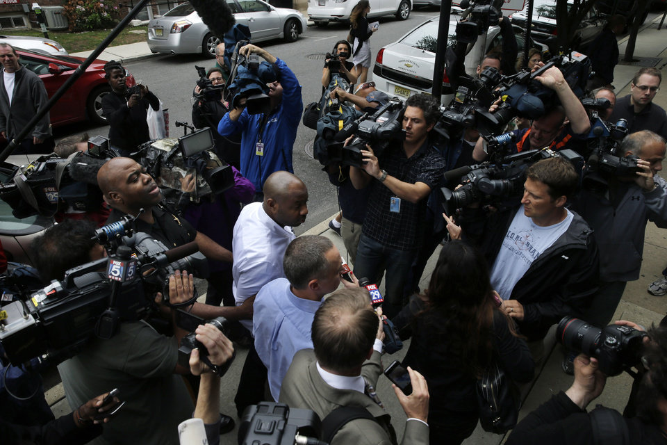 Photo - Kevin Roper, center, is surrounded by media as Middlesex County Sheriff's officers assist him as he leaves a court appearance Wednesday, June 11, 2014, in New Brunswick, N.J. Roper, a Wal-Mart truck driver from Georgia, was charged with death by auto and four counts of assault by auto in the wake of a deadly chain-reaction crash on the New Jersey Turnpike early Saturday, June 7, 2014, that killed comedian James McNair and left actor-comedian Tracy Morgan and two others critically injured.   (AP Photo/Mel Evans)