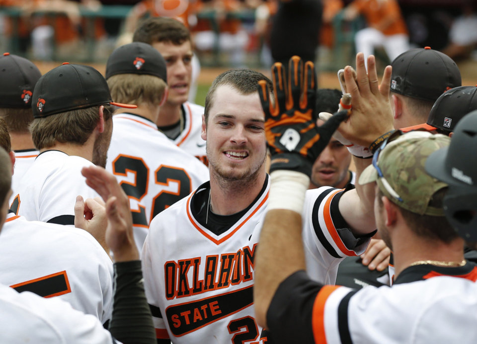 Photo - Oklahoma State's Conor Costello, center, gets high-fives from teammates after hitting a two-run home run in the second inning of a semifinal against Texas in the Big 12 NCAA college baseball tournament in Oklahoma City, Saturday, May 24, 2014. AP Photo/Sue Ogrocki)