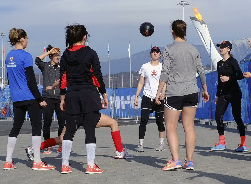 Photo - Members of the Canadian women's ice hockey team warm up outside before their game against the United States during the 2014 Winter Olympics women's ice hockey tournament at Shayba Arena, Wednesday, Feb. 12, 2014, in Sochi, Russia. (AP Photo/J. David Ake)
