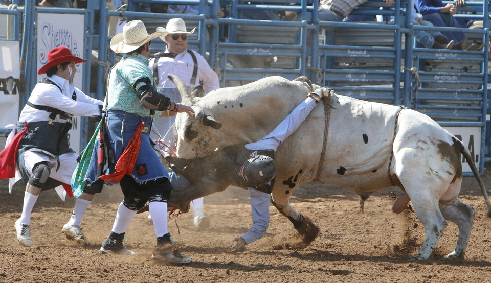 Photo - Luke Hamilton, from Coweta, OK, gets caught up in his rigging during the Bull Riding event during Tuesday's performances at the International Youth Finals Rodeo at the Shawnee Heart of Oklahoma Exposition Center in Shawnee, OK, Tuesday, July 8, 2014,  Photo by Paul Hellstern, The Oklahoman