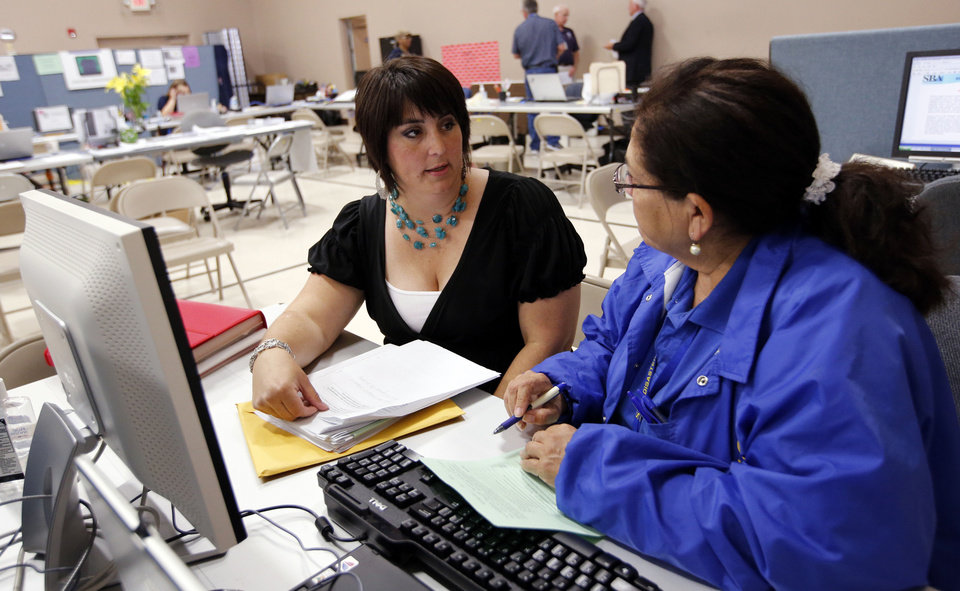 Photo - Heather Thompson, left, gets help from SBA team member Linda Lamphear at the disaster recovery center at Capitol Hill Baptist Church on Wednesday, July 17, 2013, in Oklahoma City, Okla.  Photo by Steve Sisney, The Oklahoman