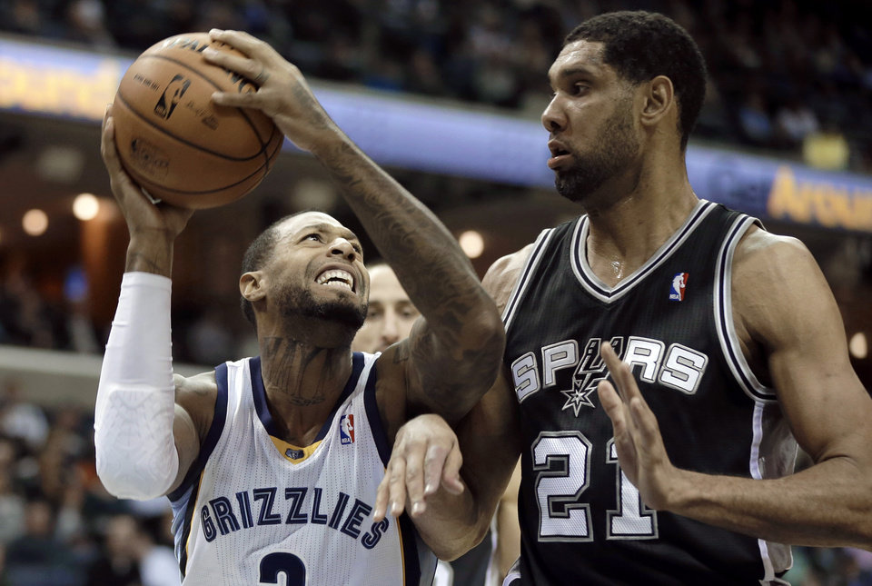 San Antonio Spurs' Tim Duncan (21), of U.S. Virgin Islands, defends against Memphis Grizzlies' James Johnson in the first half of an NBA basketball game in Memphis, Tenn., Tuesday, Jan. 7, 2014. (AP Photo/Danny Johnston)