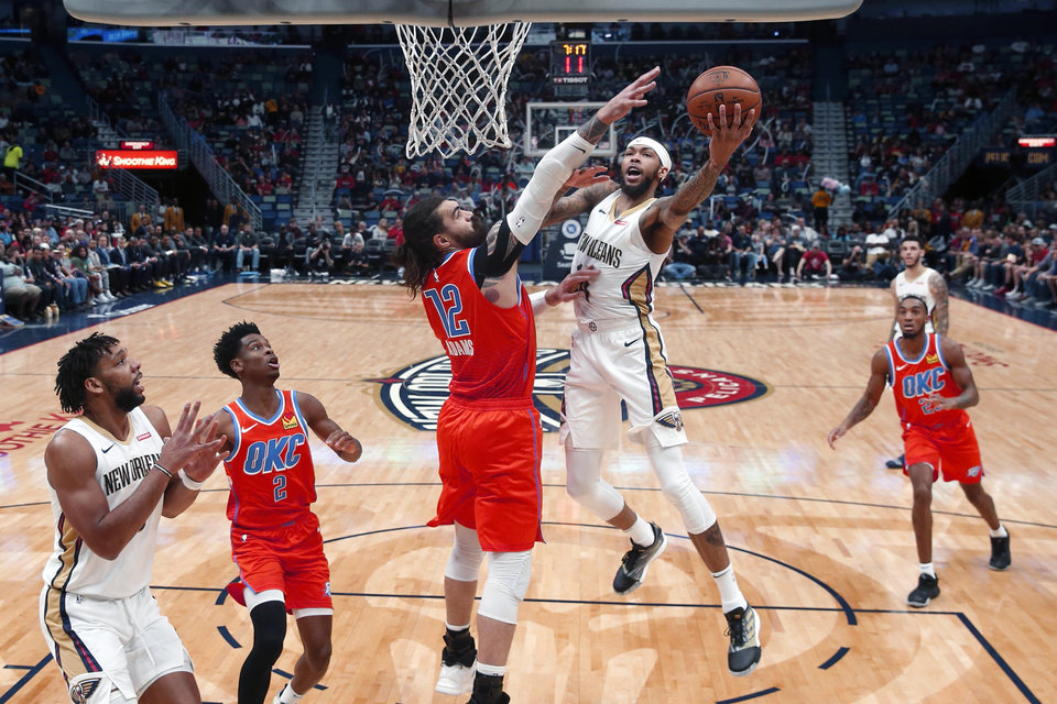 Photo - New Orleans Pelicans forward Brandon Ingram (14) goes to the basket against Oklahoma City Thunder center Steven Adams (12) in the first half of an NBA basketball game in New Orleans, Sunday, Dec. 1, 2019. (AP Photo/Gerald Herbert)