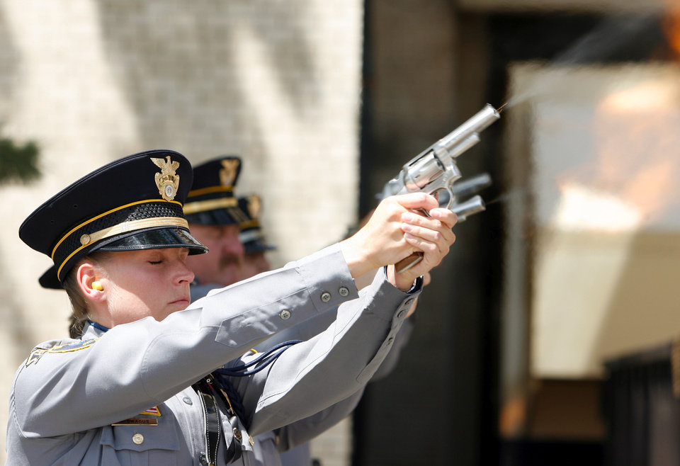 Photo - Kelly Dragus, wife Jonathan Dragus--the last Oklahoma City police officer killed in the line of duty--fires her pistol with other members of the honor guard as fallen officers are remembered at a memorial in front of Oklahoma City Police Headquarters in Oklahoma City, Oklahoma on Friday, May 9, 2008.   BY STEVE SISNEY, THE OKLAHOMAN