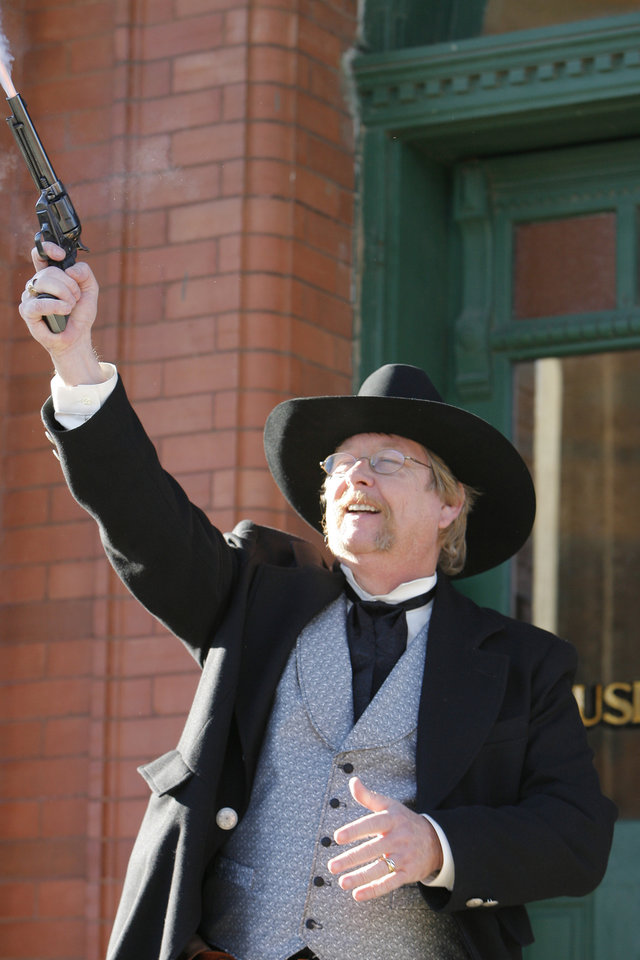 Photo - Hugh Scott fires a pistol in the air as his grandfather, Dr. Hugh Scott, did 100 years ago announcing that Oklahoma had become a state, Friday, November 16, 2007.  By David McDaniel, The Oklahoman