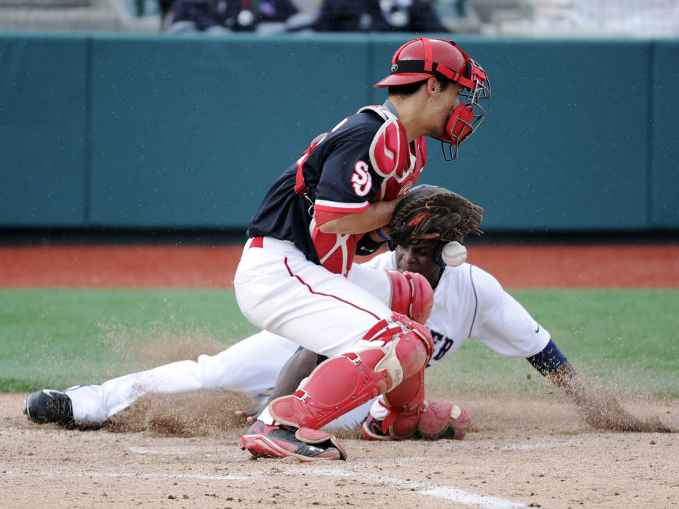 Photo - Xavier's Michael Moore scores on a double by Mitch Elliott as St. John's catcher Tyler Sanchez, left, cannot handle the throw during the third inning of an NCAA college baseball game in the Big East tournament Friday, May 23, 2014, in New York. (AP Photo/Bill Kostroun)