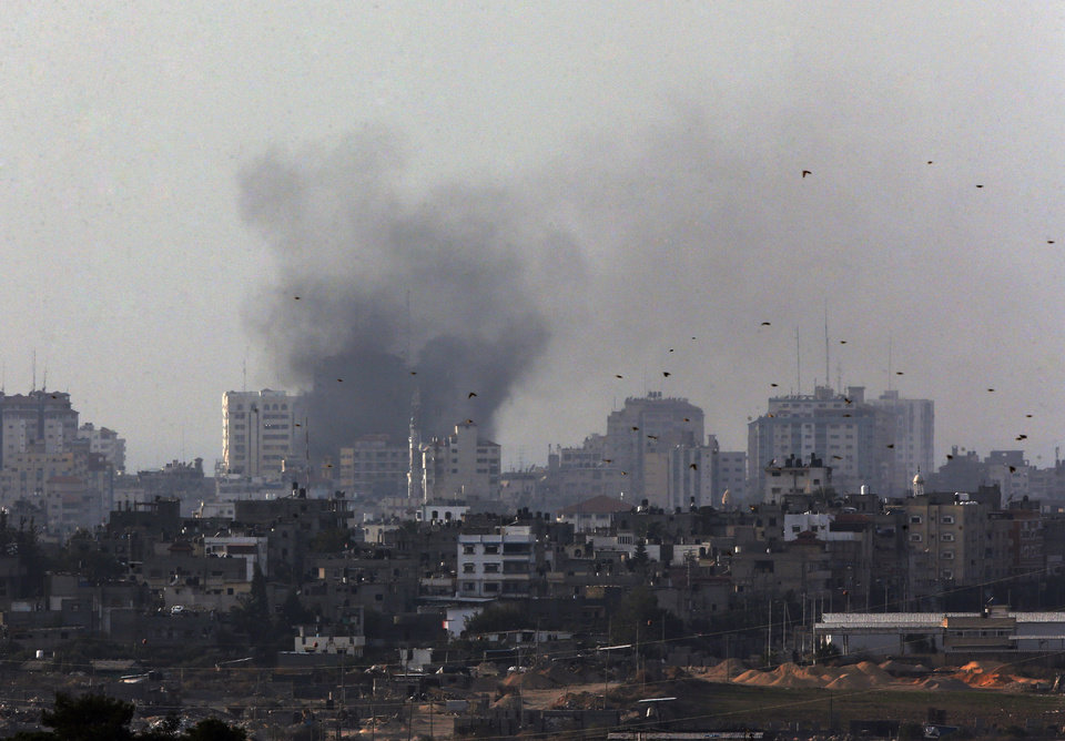 Photo -   Birds fly as a plume of smoke is seen over central Gaza Strip, after an airstrike by Israeli forces, as seen from the Israel Gaza border, Monday, Nov. 19, 2012. Israeli aircraft struck crowded areas in the Gaza Strip and killed a senior militant with a missile strike on a media center Monday, driving up the Palestinian death toll to 96, as Israel broadened its targets in the 6-day-old offensive meant to quell Hamas rocket fire on Israel. (AP Photo/Lefteris Pitarakis)