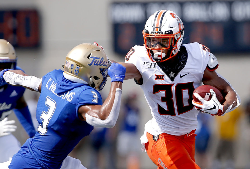 Photo - Oklahoma State's Chuba Hubbard (30) tries to get by Tulsa's Cristian Williams (3) in the first quarter during a college football game between the Oklahoma State University Cowboys (OSU) and the University of Tulsa Golden Hurricane (TU) at H.A. Chapman Stadium in Tulsa, Okla., Saturday, Sept. 14, 2019. [Sarah Phipps/The Oklahoman]