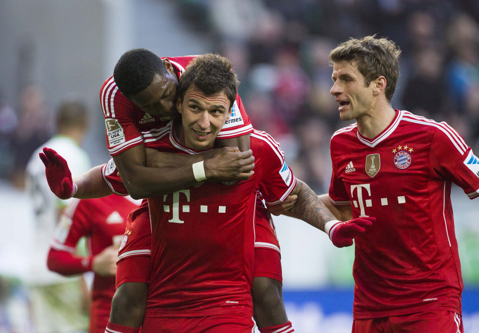 Photo - Bayern's Mario Mandzukic of Croatia, center, celebrates  after scoring his side's 3rd goal with Bayern's David Alaba of Austria, left, and Bayern's Thomas Mueller, right, during the German Bundesliga soccer match between VfL Wolfsburg and Bayern Munich in Wolfsburg, Germany, Saturday, March 8, 2014. (AP Photo/Gero Breloer)