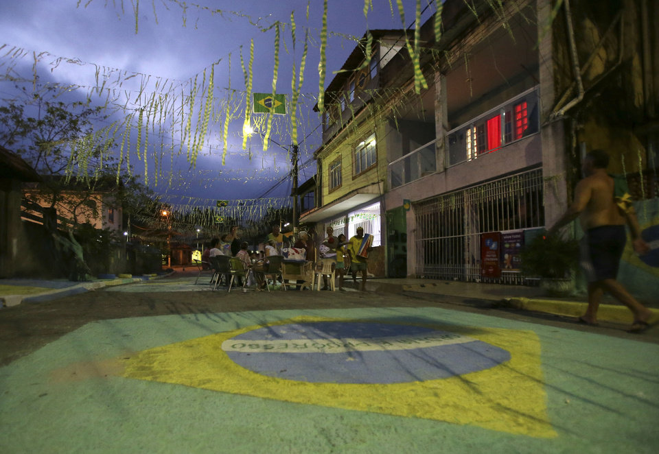 Photo - Residents watch from the middle of the street, the World Cup group A soccer match between Mexico and Brazil on a television set up on a nearby sidewalk, in Mangaratiba, Brazil, Tuesday, June 17, 2014. Mexico went on to hold host Brazil to a 0-0 draw. A street chalk drawing representing Brazil's national flag is pictured in the foreground. (AP Photo/Antonio Calanni)