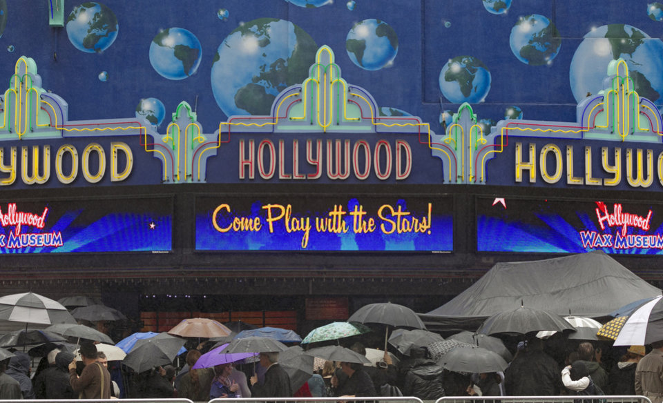 Pedestrians line up under the rain outside the Hollywood Wax museum  in the Hollywood district of Los Angeles Friday, Nov. 30, 2012. A series of storm systems will continue to move across southwestern California through Monday morning. (AP Photo/Damian Dovarganes)