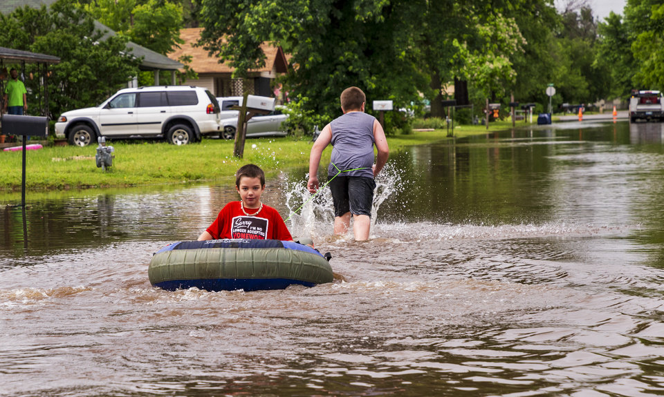 Photo - Allik Reed pulls his brother Skyler through the water on the flooded street after heavy rains flooded areas in El Reno, Okla. on Tuesday, May 21, 2019.  [Chris Landsberger/The Oklahoman]