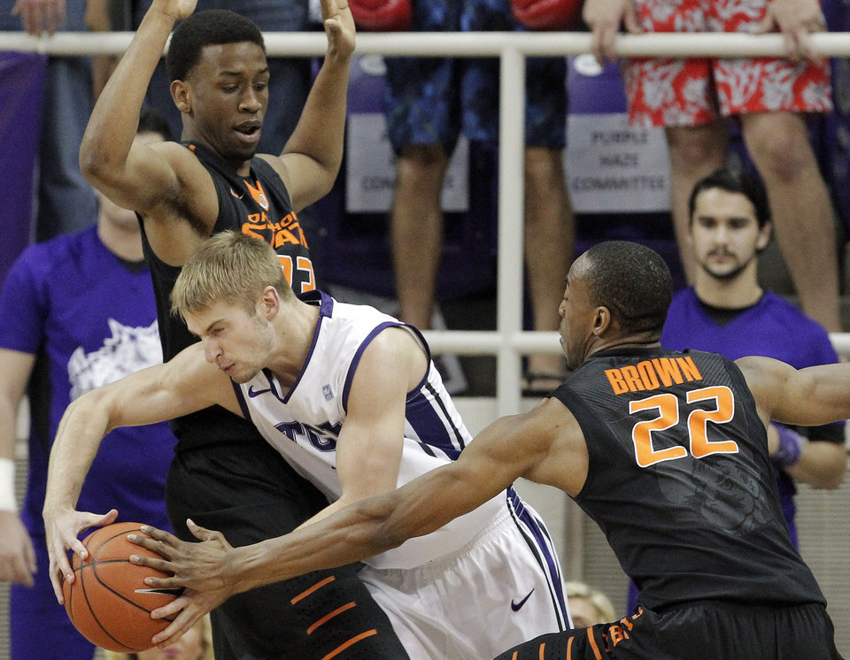 Photo - TCU guard Christian Gore, center, battles Oklahoma State's Leyton Hammonds, left, and Markel Brown (22) in the first half of an NCAA college basketball game, Monday, Feb. 24, 2014, in Fort Worth, Texas. (AP Photo/Brandon Wade)