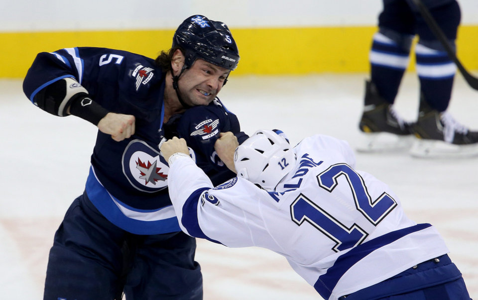 Photo - Winnipeg Jets' Mark Stuart (5) fights Tampa Bay Lightning's Ryan Malone (12) during the first period of an NHL hockey game Tuesday, Jan. 7, 2014, in Winnipeg, Manitoba. (AP Photo/The Canadian Press, Trevor Hagan)