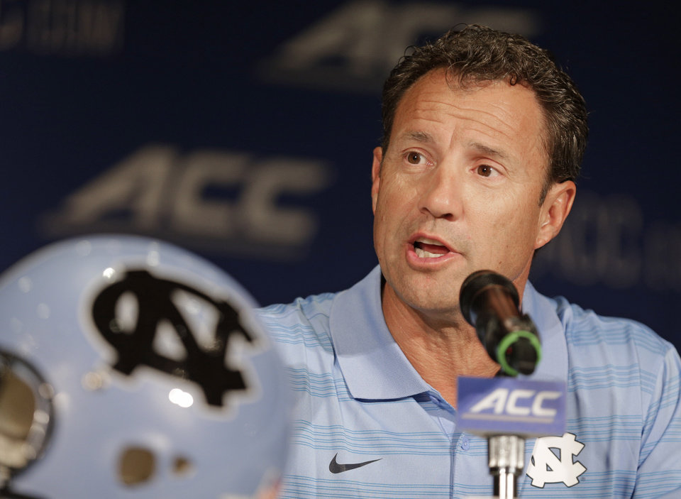 Photo - FILE - In this July 21, 2014, file photo, North Carolina coach Larry Fedora answers a question during a news conference at the Atlantic Coast Conference football kickoff in Greensboro, N.C. Fedora says the team has suspended four players for this weekend's season opener, a day after a report of an alleged hazing altercation left a walk-on receiver with a possible concussion. Fedora said Wednesday, Aug. 27, the four players were suspended for a