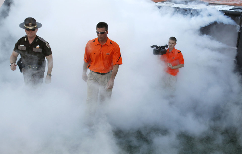 Photo - OSU head coach Mike Gundy walks onto the field before the college football game between the Oklahoma State University Cowboys (OSU) and the Troy University Trojans at Boone Pickens Stadium in Stillwater, Okla., Saturday, Sept. 11, 2010. Photo by Sarah Phipps, The Oklahoman
