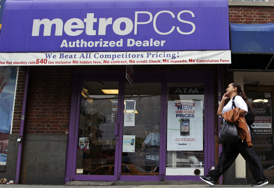 A pedestrian talks on a cellular phone Wednesday as he walks past a MetroPCS authorized dealer in New York. AP Photo <strong>Mary Altaffer</strong>