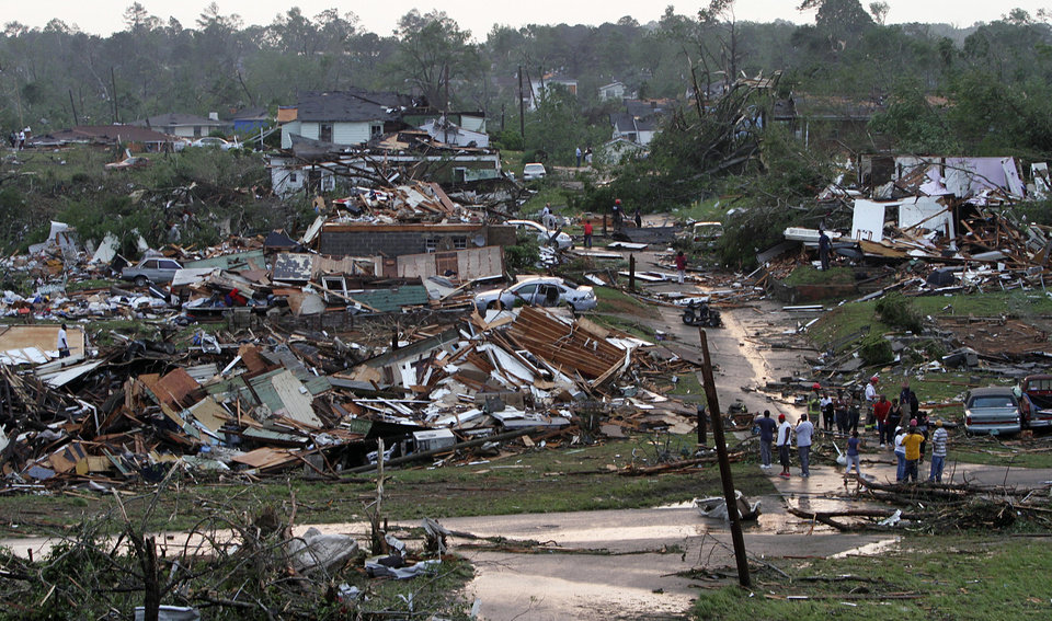 Photo - Residents survey the destruction after a tornado hit Pratt City, Ala. just north of downtown Birmingham, Ala. on Wednesday, April 27, 2011. A wave of severe storms laced with tornadoes strafed the South on Wednesday, killing at least 16 people around the region and splintering buildings across swaths of an Alabama university town. (AP Photo/Butch Dill)