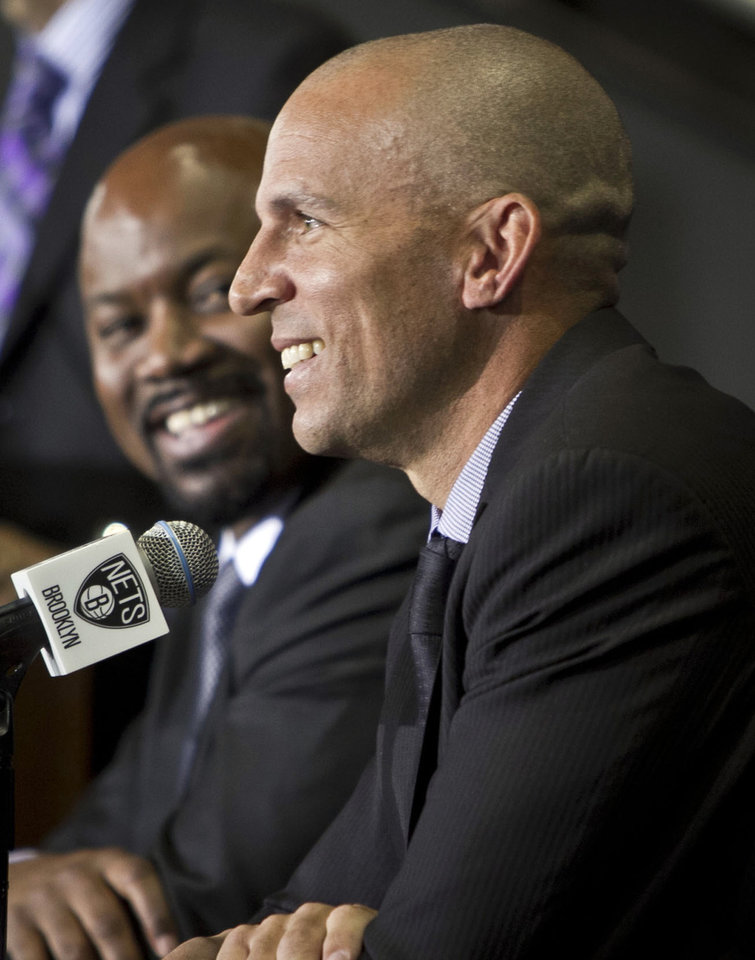 Photo - Brooklyn Nets general manger Billy King, left, smiles as head coach Jason Kidd speaks after Kidd was introduced as the team's new coach during an NBA basketball news conference Thursday, June 13, 2013, in New York.   (AP Photo/Bebeto Matthews)