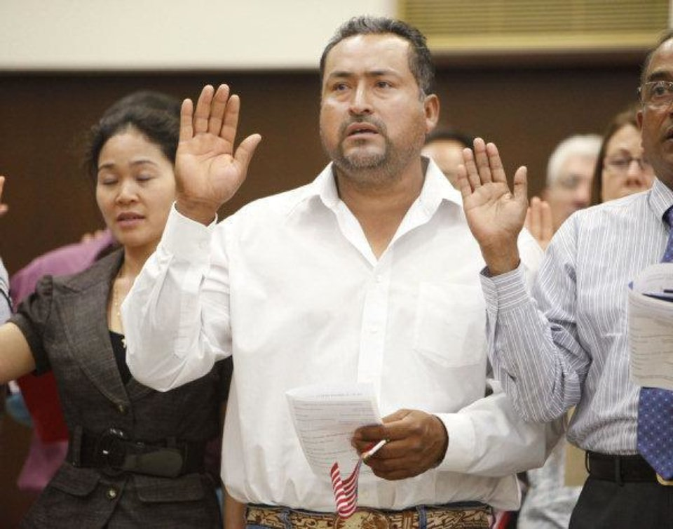 Photo - Former Mexican citizen Ernesto Rosas takes the oath of U.S. citizenship during a June 24 naturalization ceremony at the federal courthouse in Oklahoma City.  PAUL HELLSTERN - THE OKLAHOMAN