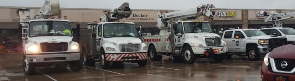 Photo -  Trucks from a company that is helping Oklahoma Gas and Electric restore power in central Oklahoma are staged at a strip mall in southern Logan County early Thursday. [JACK MONEY/THE OKLAHOMAN]