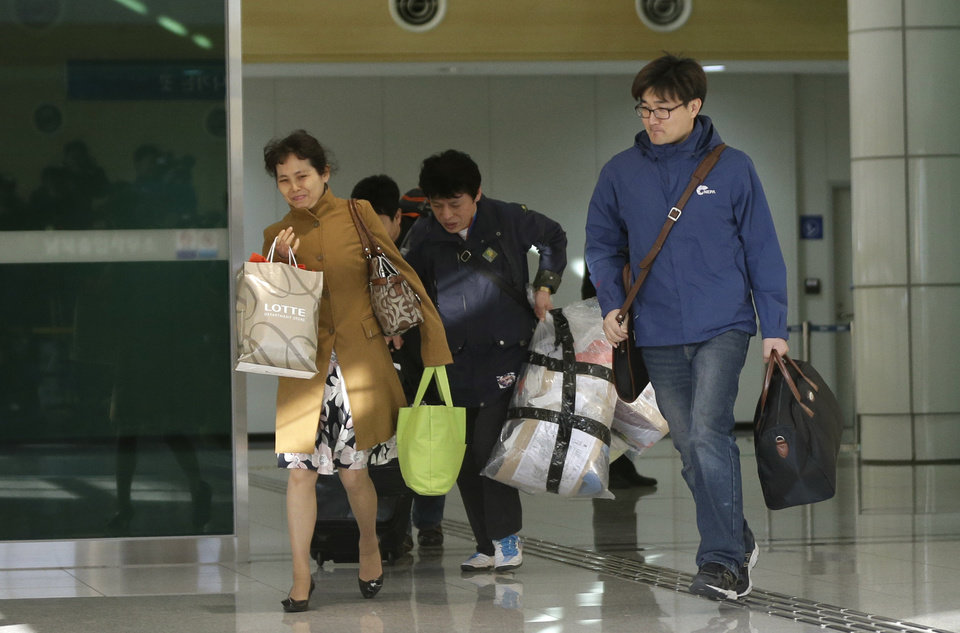 Photo - South Koreans arrive with their belongings from North Korea's Kaesong at the customs, immigration and quarantine office near the border village of Panmunjom, which has separated the two Koreas since the Korean War, in Paju, north of Seoul, South Korea, Tuesday, April 9, 2013. A few hundred South Korean managers, some wandering among quiet assembly lines, were all that remained Tuesday at the massive industrial park run by the rival Koreas after North Korea pulled its more than 50,000 workers from the complex. Others stuffed their cars full of goods before heading south across the Demilitarized Zone that divides the nations. (AP Photo/Lee Jin-man)