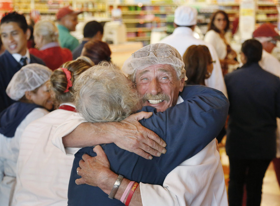 Photo - Market Basket meat manager Bob Dietz, of Methuen, Mass., front right, hugs cashier Mary Olson, of Chelsea, Mass., after watching a televised speech by restored Market Basket CEO Arthur T. Demoulas at a store location, Thursday, Aug. 28, 2014, in Chelsea. A six-week standoff between thousands of employees of the New England supermarket chain and management has ended with the news that the beloved Demoulas is back in control after buying the entire company. Demoulas made his speech to workers in Tewksbury, Mass. (AP Photo/Steven Senne)