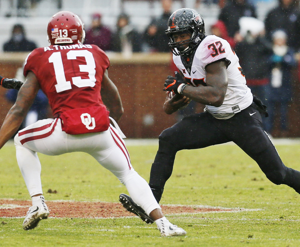 Photo - Oklahoma State's Chris Carson (32) runs for a first down on fourth down in the fourth quarter as Oklahoma's Ahmad Thomas (13) defends during the Bedlam college football game between the Oklahoma Sooners (OU) and the Oklahoma State Cowboys (OSU) at Gaylord Family - Oklahoma Memorial Stadium in Norman, Okla., Saturday, Dec. 3, 2016. OU won 38-20. Photo by Nate Billings, The Oklahoman