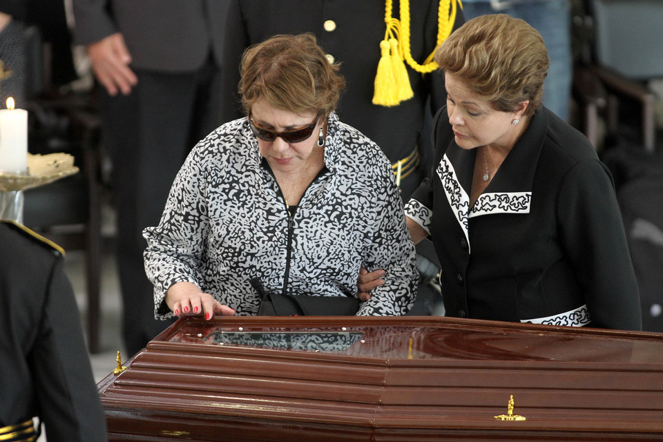 Photo - Brazil's President Dilma Rousseff , right, and the wife of Brazil's architect Oscar Niemeyer, Vera Lucia, left, stand before the coffin containing Niemeyer's remains during a memorial at the Planalto presidential palace, in Brasilia, Brazil, Thursday, Dec. 6, 2012. Niemeyer, 104, the groundbreaking architect who designed Brazil's futuristic capital and much of the United Nations complex, died Wednesday night in Rio de Janeiro, the seaside city where he was born and where his remains will be buried after he is honored with a service in Brasilia at the presidential palace he designed. (AP Photo/Eraldo Peres)