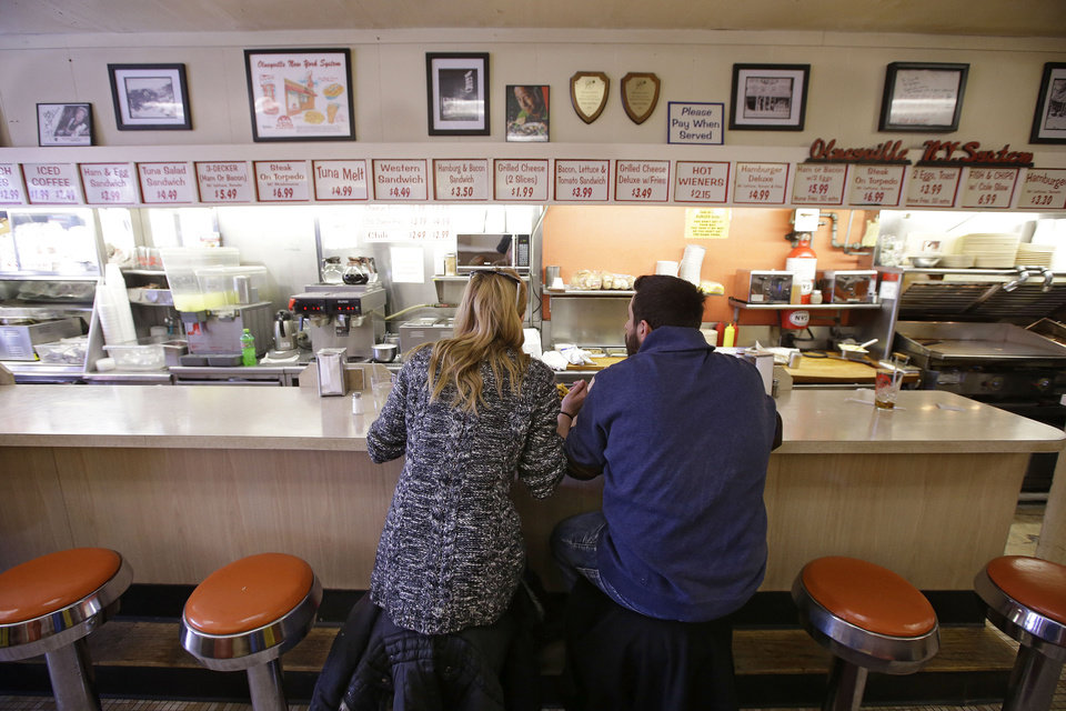 Photo - TAKES OUT HOT DOG REFERENCE - In this Monday, March 3, 2014 photo Holly Wilson and Ioanni Degaitas eat a lunch of two hot wieners, a loaded cheese burger, a grilled cheese sandwich with bacon and tomato, chile cheese fries, eggs, home fires, coffee milk and black coffee at Olneyville New York System of Providence in Providence, RI. The James Beard Foundation named the Rhode Island restaurant one of five