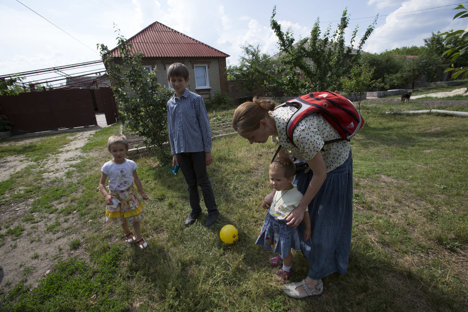 Photo - Olga Mikhailova, right, prepares her children to abandon their home in Slovyansk, Ukraine, Wednesday, May 28, 2014. In Slovyansk, a city 90 kilometers (55 miles) north of Donetsk which has seen repeated clashes over the past few weeks, with residential areas comming under mortar shelling Wednesday from government forces. A school was badly damaged and other buildings were hit, according to residents, Wednesday who told The Associated Press that several people were wounded. (AP Photo/Alexander Zemlianichenko)