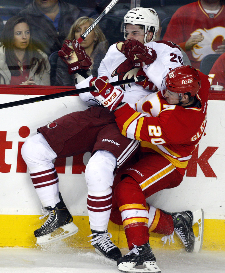 Phoenix Coyotes\' Chris Summers, left, gets checked by Calgary Flames\' Curtis Glencross during the third period of an NHL hockey game in Calgary, Alberta, Sunday, Feb. 24, 2013. (AP Photo/The Canadian Press, Jeff McIntosh)