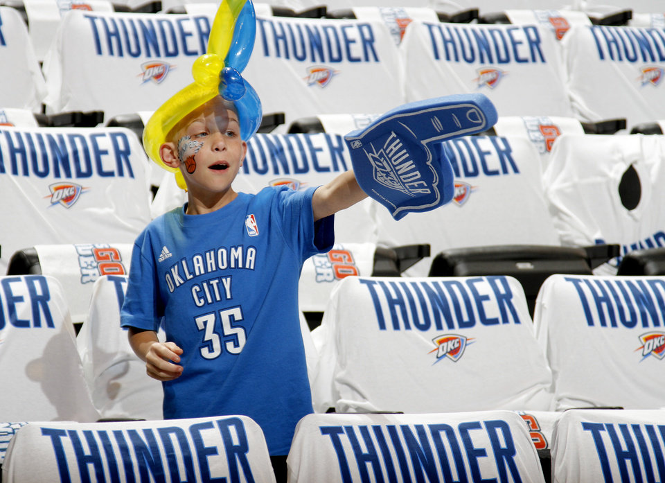 Photo - Bennett England, 11, of Lawton watches players before game five of the Western Conference semifinals between the Memphis Grizzlies and the Oklahoma City Thunder in the NBA basketball playoffs at Oklahoma City Arena in Oklahoma City, Wednesday, May 11, 2011. Photo by Bryan Terry, The Oklahoman