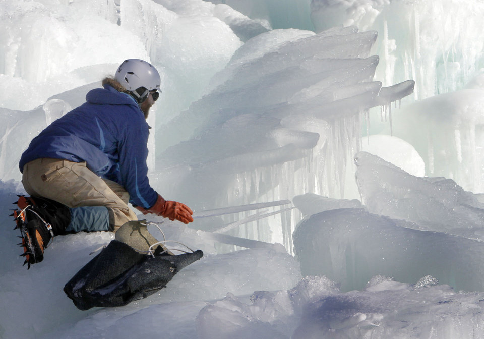 Photo - In this photo taken Wednesday Jan. 8, 2014 Cory Livingood places icicles on the top of his ice castle at the base of the Loon Mountain ski resort in Lincoln, N.H. The ice castle begins to grow in the fall when the weather gets below freezing and thousands of icicles are made and harvested then placed around sprinkler heads and sprayed with water.  The castle will continue to grow as long as the temperatures stay below freezing. (AP Photo/Jim Cole)