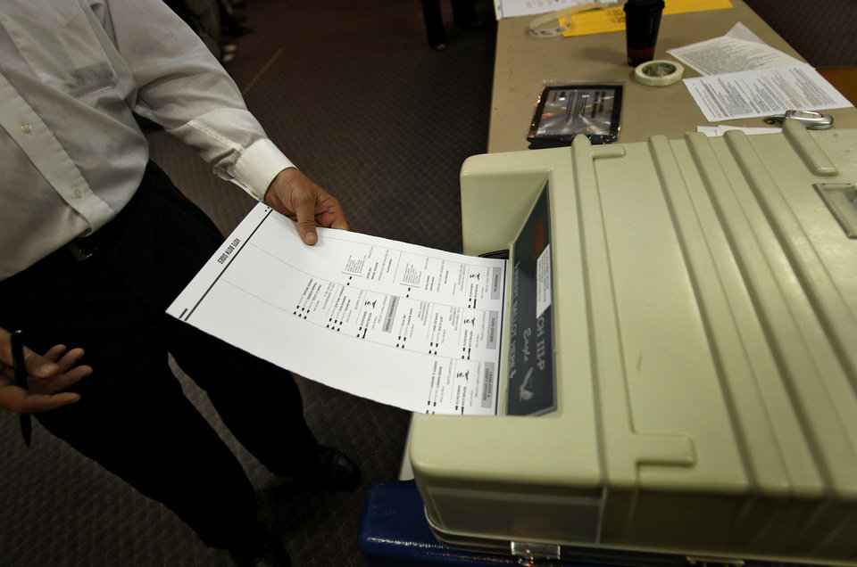 Photo - A voter cast a ballot into the polling machine at the Presidential election polling location at Canadian Hills Church of the Nazarene on Tuesday, Nov. 4, 2008, in Yukon, Okla.   BY CHRIS LANDSBERGER, THE OKLAHOMAN