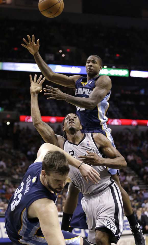 Photo - San Antonio Spurs' Kawhi Leonard (2) crashes into Memphis Grizzlies' Marc Gasol (33), of Spain, as he tries to shoot during the second half of an NBA basketball game, Wednesday, Oct. 30, 2013, in San Antonio. Grizzlies' Ed Davis is at top. (AP Photo/Eric Gay)