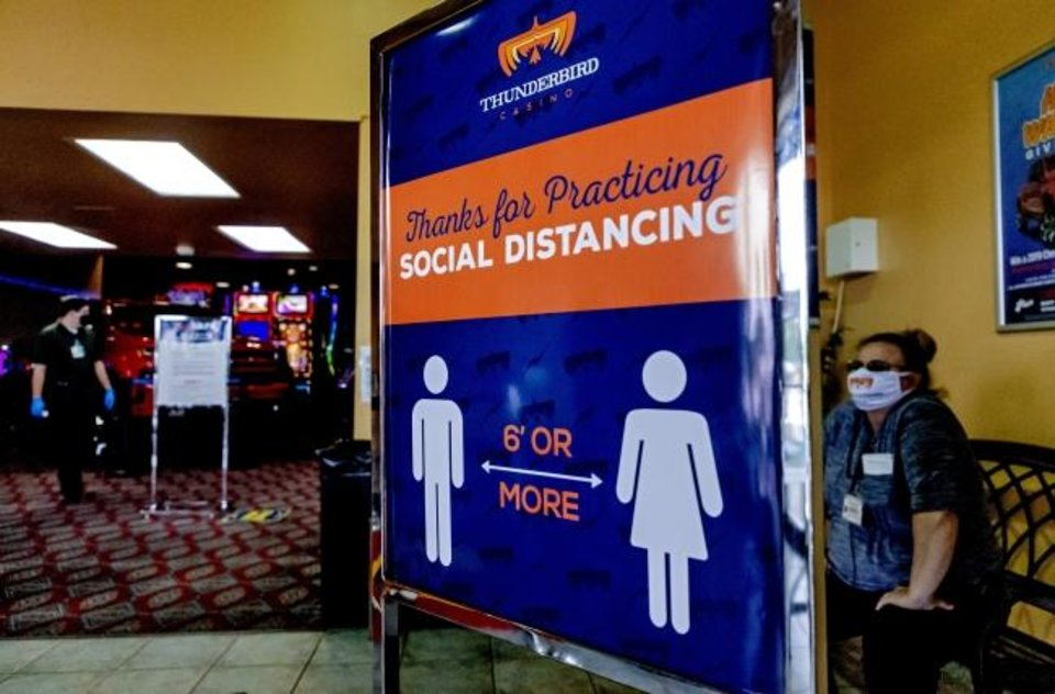Photo - Social distancing signs displayed on the floor for patrons to using while playing games at the Thunderbird Casino for its soft reopening on Monday, May 11, 2020, in Norman, Okla. The casino is operating at a third of its capacity and spacing out machines six feet apart while implementing temp checks at the door and enforcing masks. [Chris Landsberger/The Oklahoman]