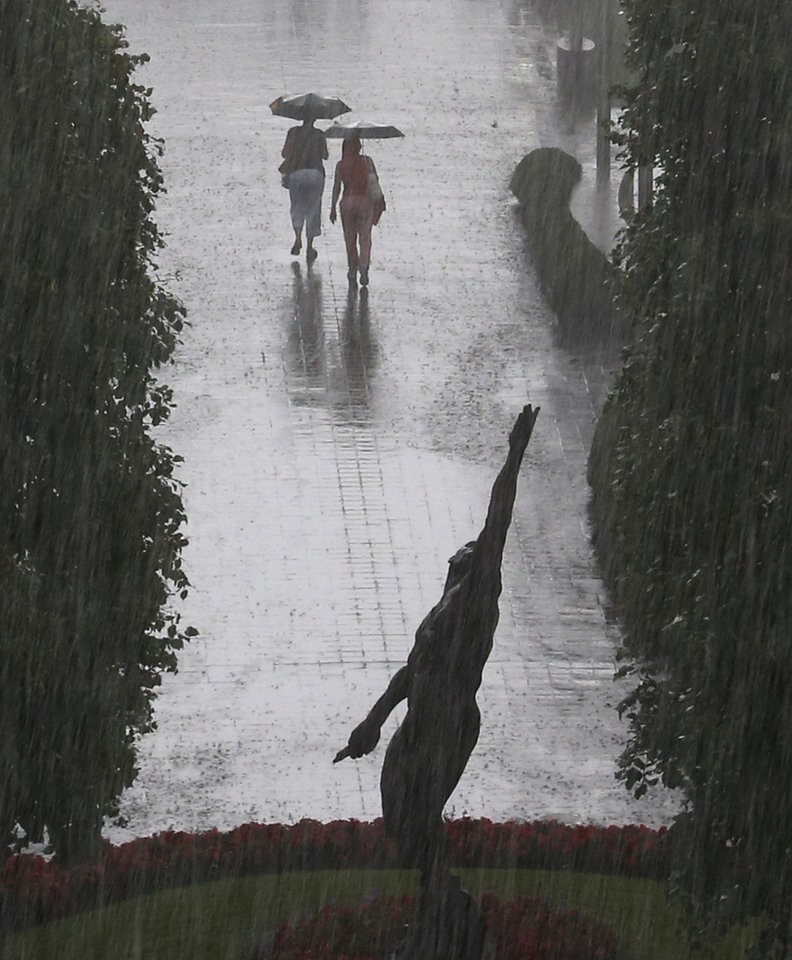 Photo - Tennis fans exit the Billie Jean King National Tennis Center as a heavy rain falls suspending play of the 2014 U.S. Open tennis tournament, Sunday, Aug. 31, 2014, in New York. (AP Photo/Kathy Willens)