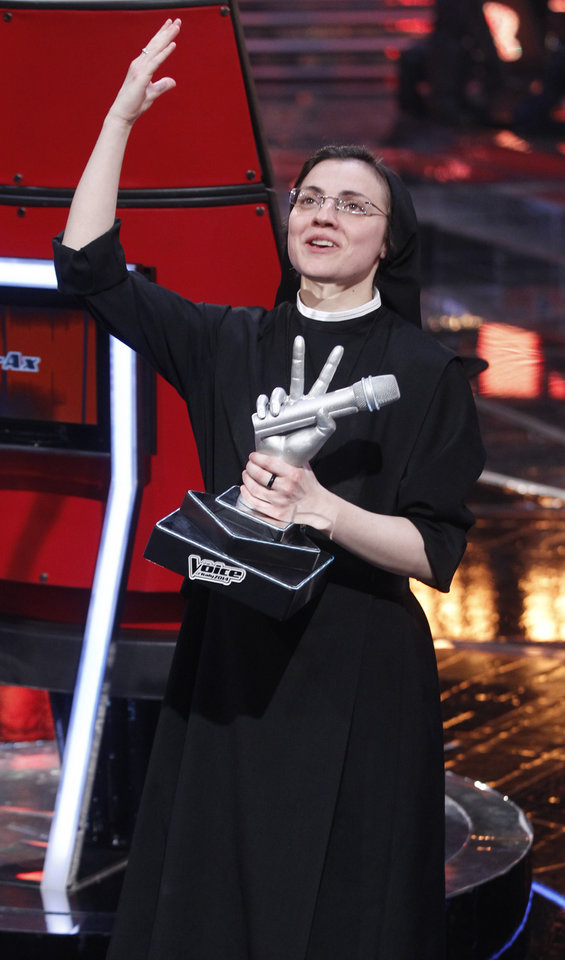 Photo - Sister Cristina Scuccia poses with the trophy  on the stage after winning the final of the Italian version of the TV talent show