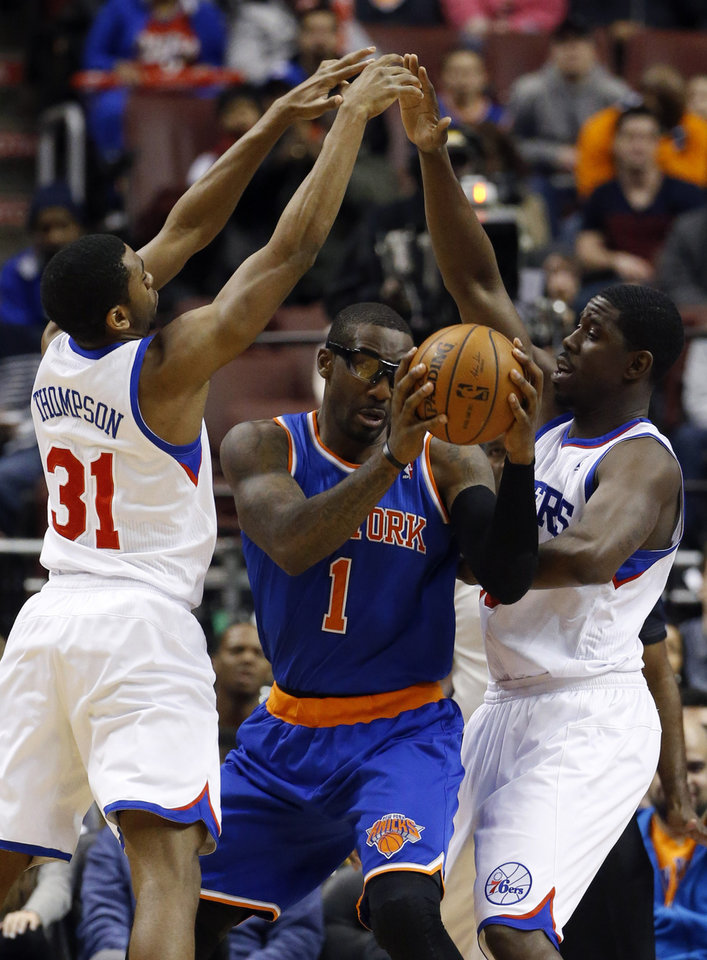 Photo - New York Knicks' Amar'e Stoudemire, center, tries to squeeze past Philadelphia 76ers' Hollis Thompson, left, and Henry Sims during the second half of an NBA basketball game, Friday, March 21, 2014, in Philadelphia. New York won 93-92. (AP Photo/Matt Slocum)