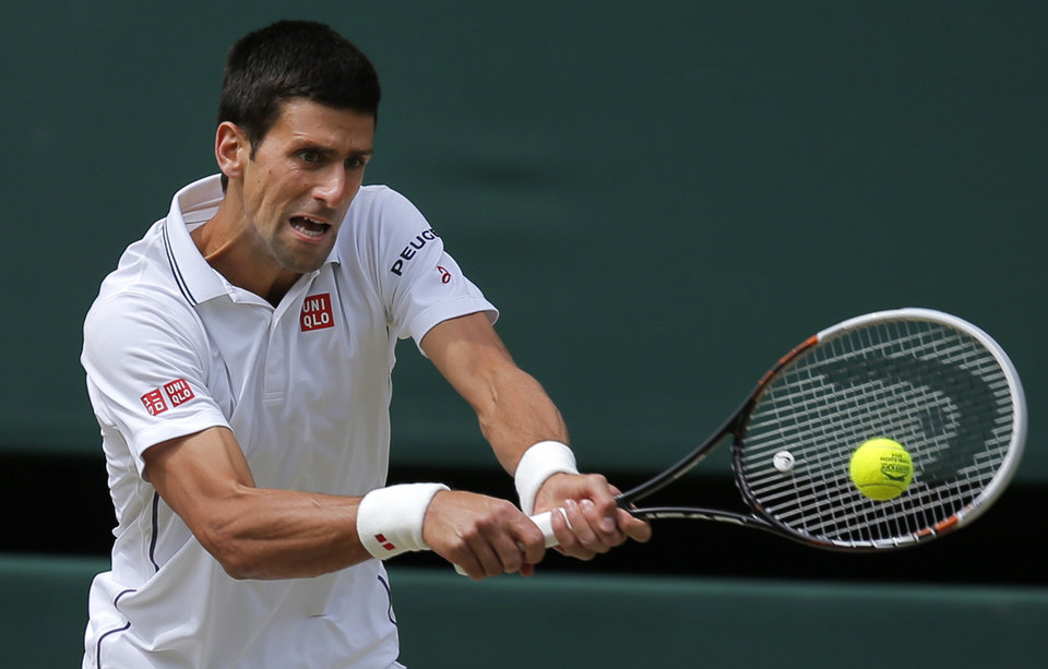 Novak Djokovic of Serbia plays a return to Roger Federer of Switzerland during their men\'s singles final at the All England Lawn Tennis Championships in Wimbledon, London, Sunday July 6, 2014. (AP Photo/Pavel Golovkin)