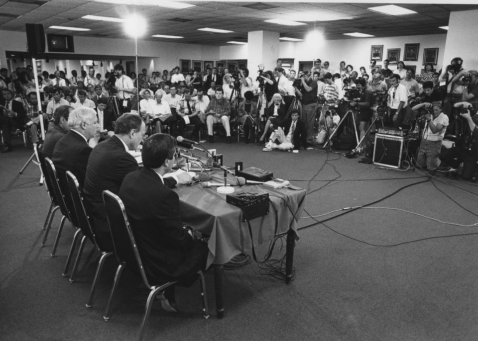 Photo - Barry Switzer, seated at table third from left, was accustomed to packed stadiums and rooms filled with reporters during his years as head football coach at the University of Oklahoma. But it was a different atmosphere June 20, 1989 in Norman when Switzer told the room full of reporters that he was resigning. PHOTO BY STEVE SISNEY, The Oklahoman Archives