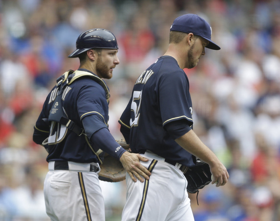 Photo - Milwaukee Brewers catcher Jonathan Lucroy encourages starting pitcher Jimmy Nelson as they walk back to the mound during the third inning of a baseball game against the St. Louis Cardinals Saturday, July 12, 2014, in Milwaukee. (AP Photo/Jeffrey Phelps)