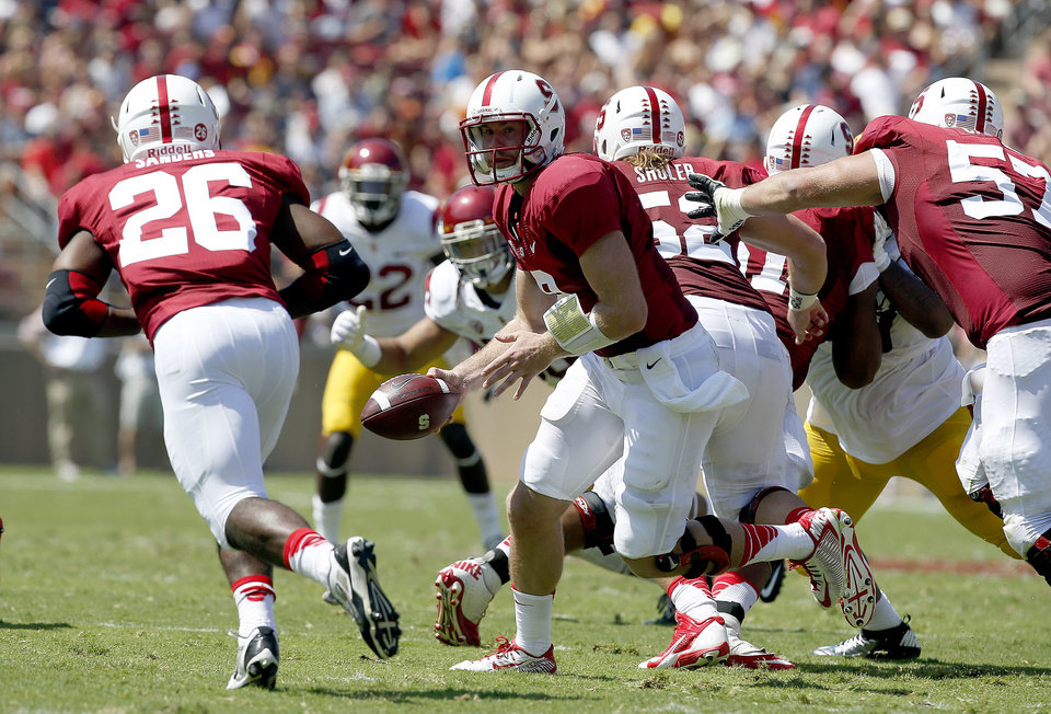 Photo - Stanford quarterback Kevin Hogan (8) hands off to running back Barry Sanders (26) against Southern California in a NCAA college football game on Saturday, Sept. 6, 2014, in Stanford, Calif. (AP Photo/Tony Avelar)