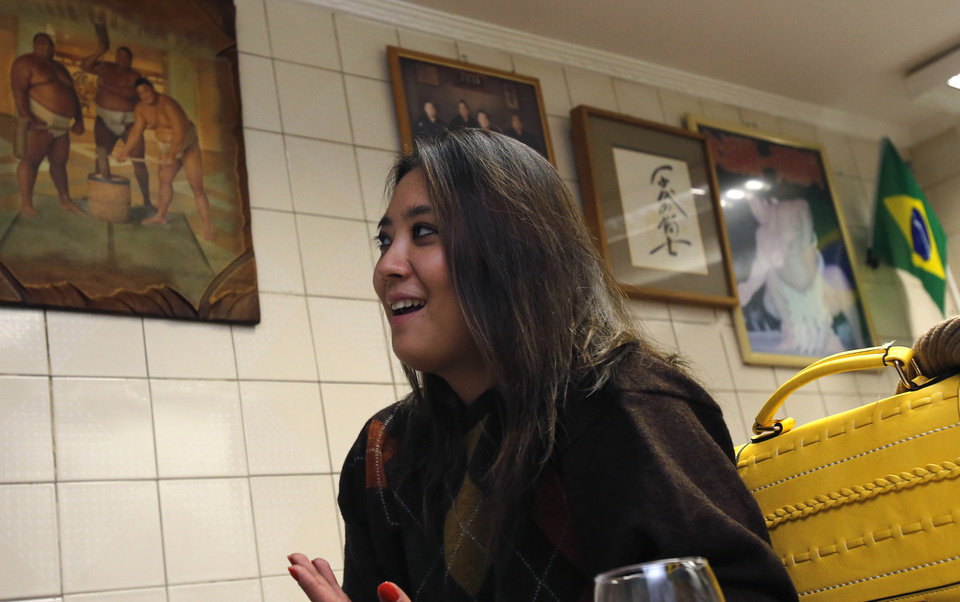 Photo - In this June 10, 2014, photo, Sao Paulo's former Miss Okinawa, Lais Miwa Higa, speaks in an interview in front of paintings of sumo and a Brazilian flag at Bar Kintaro in Sao Paulo, Brazil. The elite Sao Paulo University Master's degree student in anthropology, who is considering a PhD, has trouble being perceived among Brazilian peers as more than a Japanese geisha doll. (AP Photo/Shuji Kajiyama)
