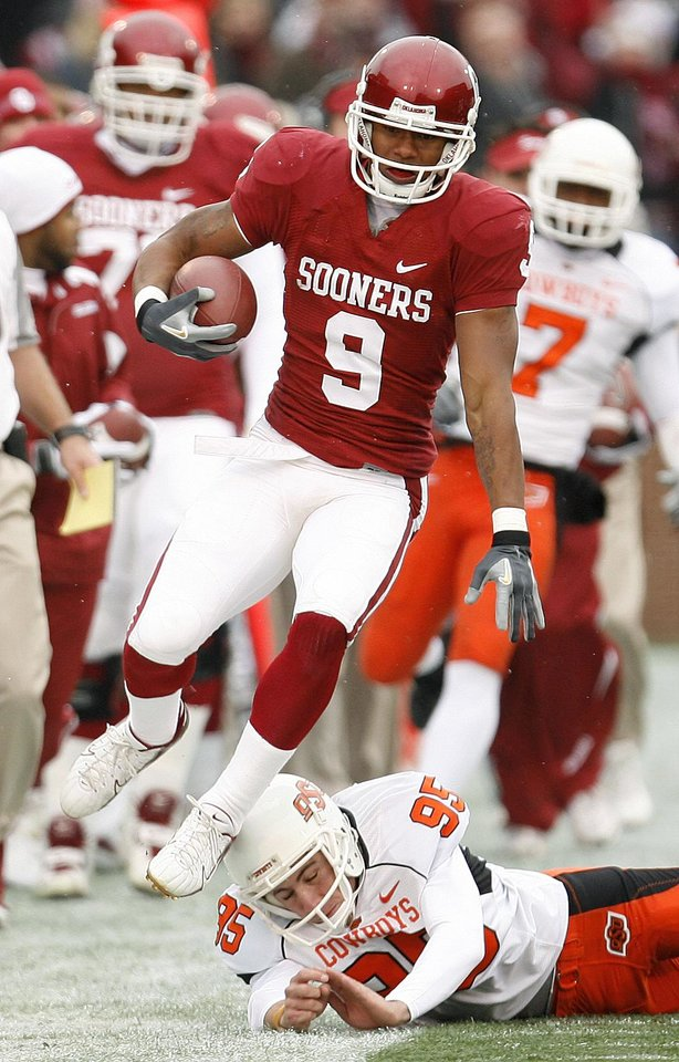 Photo - BEDLAM: Juaquin Iglesias of OU leaps over Dan Bailey of OSU during return in the first half of the college football game between the University of Oklahoma Sooners (OU) and the Oklahoma State University Cowboys (OSU) at the Gaylord Family -- Oklahoma Memorial Stadium on Saturday, Nov. 24, 2007, in Norman, Okla.  Photo By Bryan Terry, The Oklahoman ORG XMIT: KOD