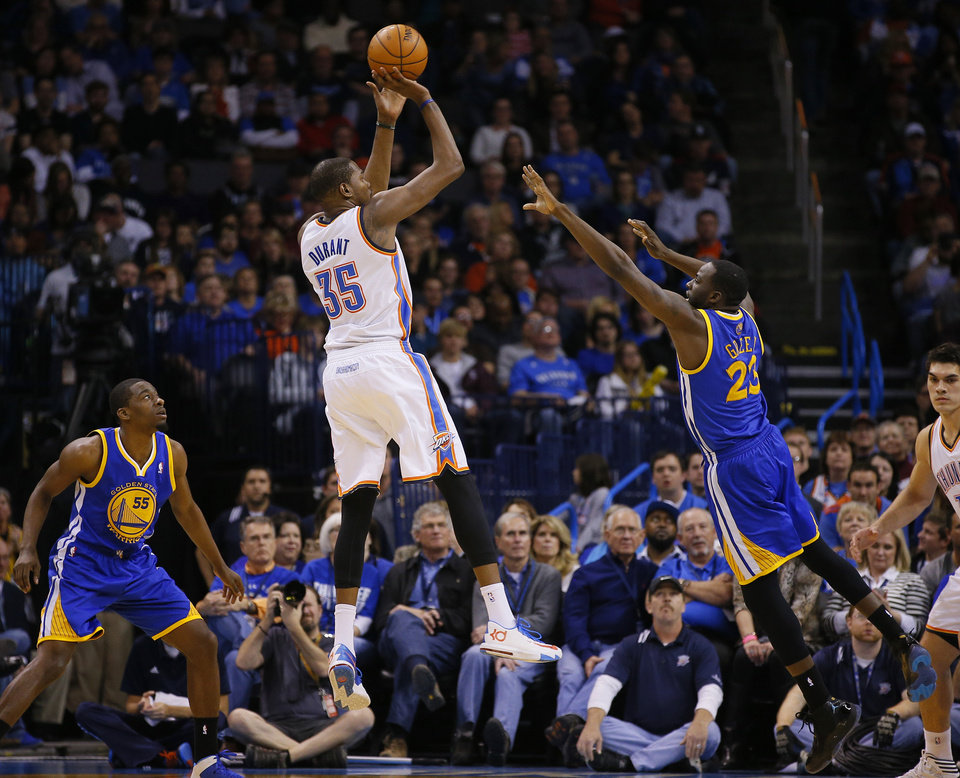 Photo - Oklahoma City's Kevin Durant (35) shoots from between Golden State's Jordan Crawford (55) and Draymond Green (23) during an NBA basketball game between the Oklahoma City Thunder and the Golden State Warriors at Chesapeake Energy Arena in Oklahoma City, Friday, Jan. 17, 2014. Oklahoma City won 127-121. Photo by Bryan Terry, The Oklahoman