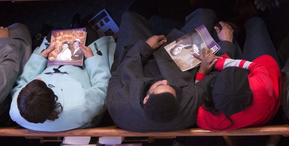 Photo - Spectators hold programs with photos of the late  Rev. Martin Luther King Jr. during the Rev. Martin Luther King Jr. holiday commemorative service at Ebenezer Baptist Church Monday, Jan. 20, 2014, in Atlanta. (AP Photo/Jason Getz)