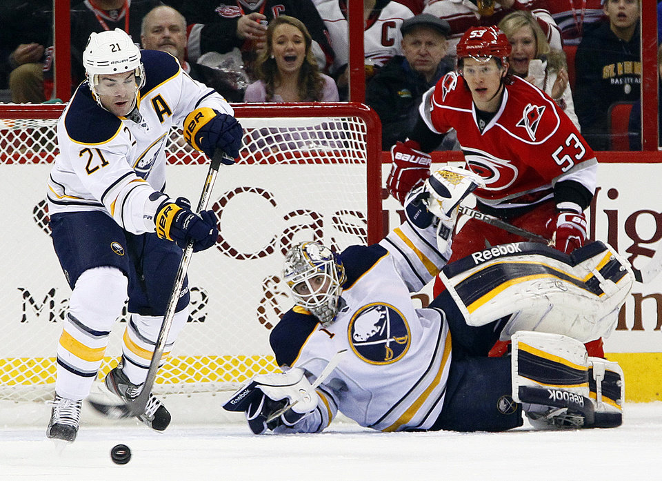 Buffalo Sabres\' Drew Stafford (21) clears the puck after goalie Jhonas Enroth (1) blocks the shot of Carolina Hurricanes\' Jeff Skinner (53) during the first period of an NHL hockey game in Raleigh, N.C., Thursday, Jan. 24, 2013. (AP Photo/Karl B DeBlaker)