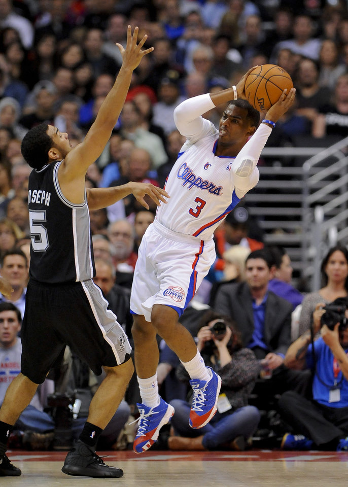 Photo - Los Angeles Clippers guard Chris Paul (3) looks around San Antonio Spurs guard Cory Joseph (5) for the open man in the first half of a NBA basketball game, Tuesday, Feb. 18, 2014, in Los Angeles.(AP Photo/Gus Ruelas)